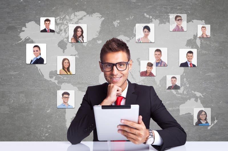 Homem de negócio de sorriso com trabalhos em rede da almofada da tabuleta foto de stock royalty free