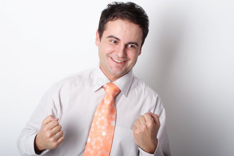 Homem de negócio de sorriso novo que mostra os punhos fotografia de stock royalty free