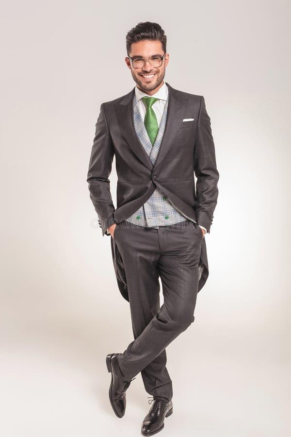 Homem de negócio de sorriso que está com suas mãos em uns bolsos imagem de stock