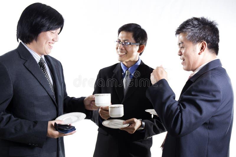 Homem de negócio de três asiáticos com a ruptura de café que tem a conversação fotografia de stock royalty free