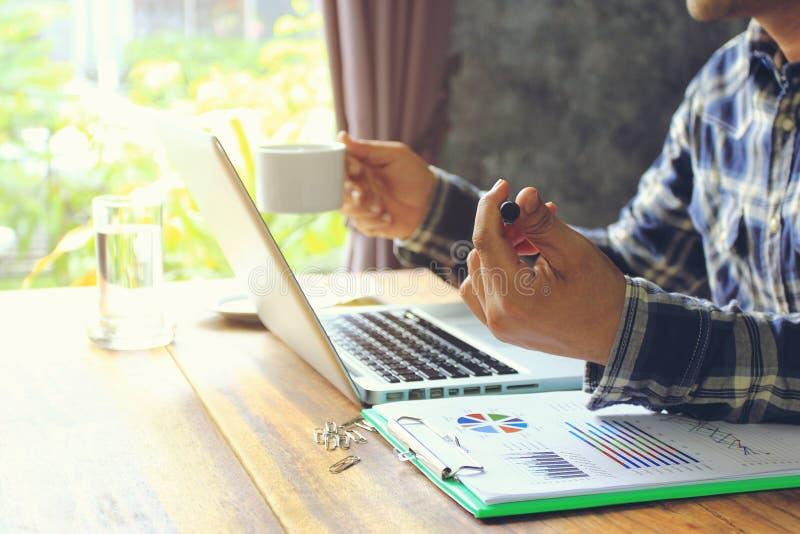 Homem de negócio do freelancer que trabalha usando o laptop e realizando penas no escritório domiciliário, na tecnologia de comun fotografia de stock royalty free