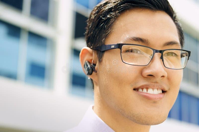 Homem de negócio do Headshot com dispositivo Handsfree de Bluetooth foto de stock royalty free