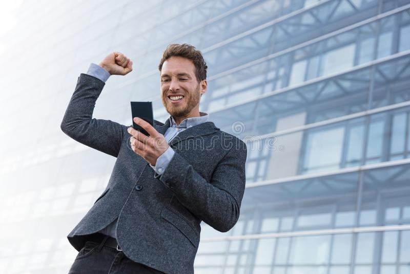 Homem de negócio do vencedor do sucesso que ganha no app do telefone celular Homem de negócios Cheering que olha o desafio ou o t fotografia de stock royalty free