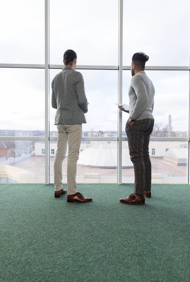 Homem de negócio dois que usa o negócio Team Coworkers Stand do centro de Coworking do tablet pc na janela panorâmico grande dian foto de stock royalty free