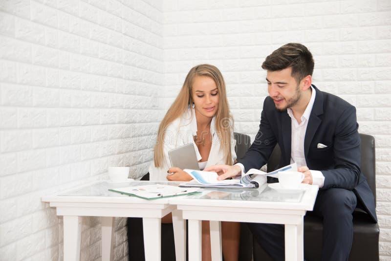 Homem de negócio e seu secretário que falam para o informe anual do ano imagens de stock royalty free