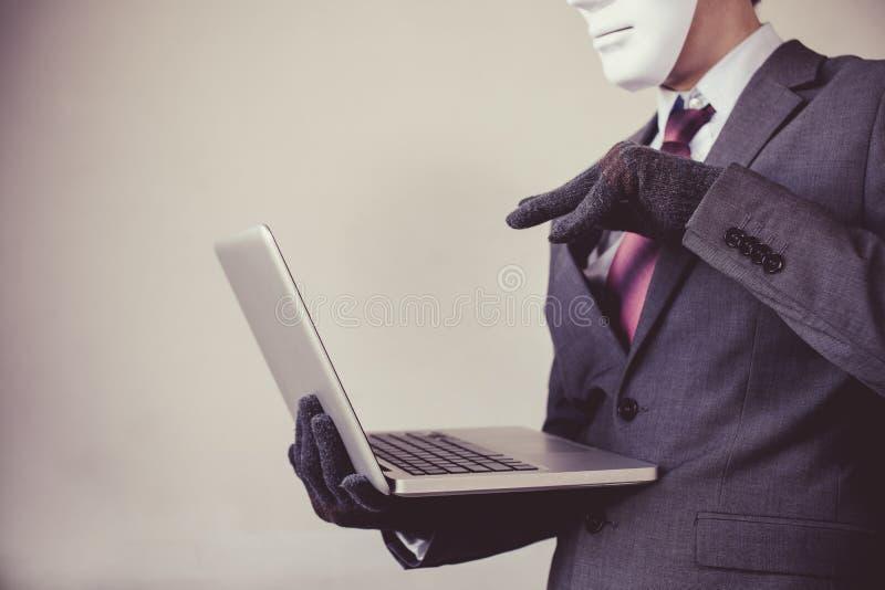 Homem de negócio em luvas da máscara branca e no computador vestindo da utilização - fraude, hacker, roubo, crime do cyber foto de stock royalty free