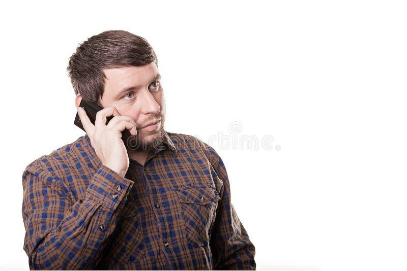 Homem de negócio em uma camisa de manta que fala no telefone isolado em w foto de stock