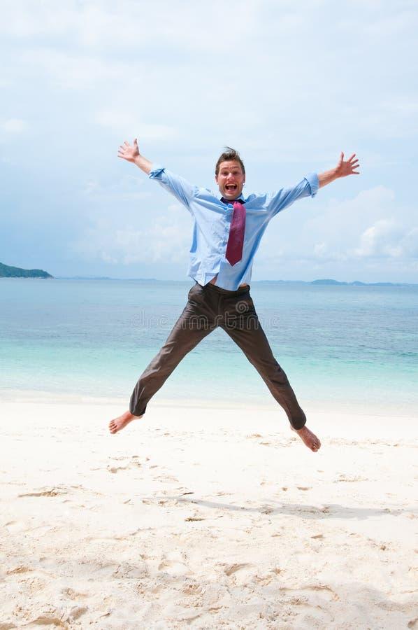 Homem de negócio engraçado que salta na praia fotos de stock