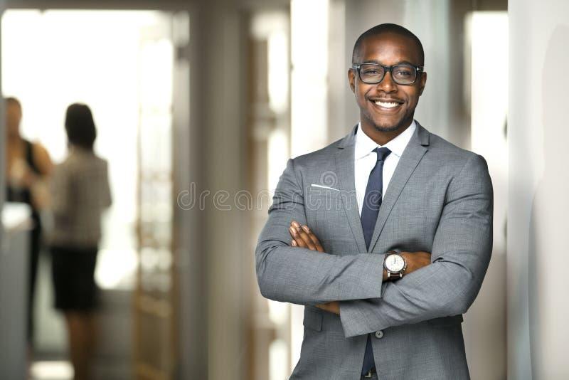 Homem de negócio executivo afro-americano alegre considerável no escritório do espaço de trabalho foto de stock royalty free