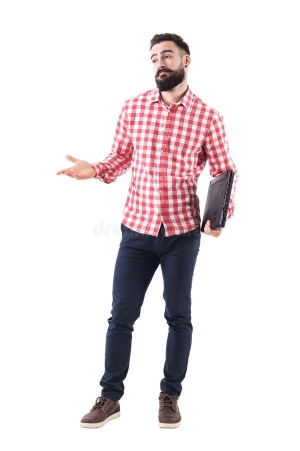 Homem de negócio farpado adulto novo confuso com o portátil sob os braços que shrugging e que olha afastado foto de stock