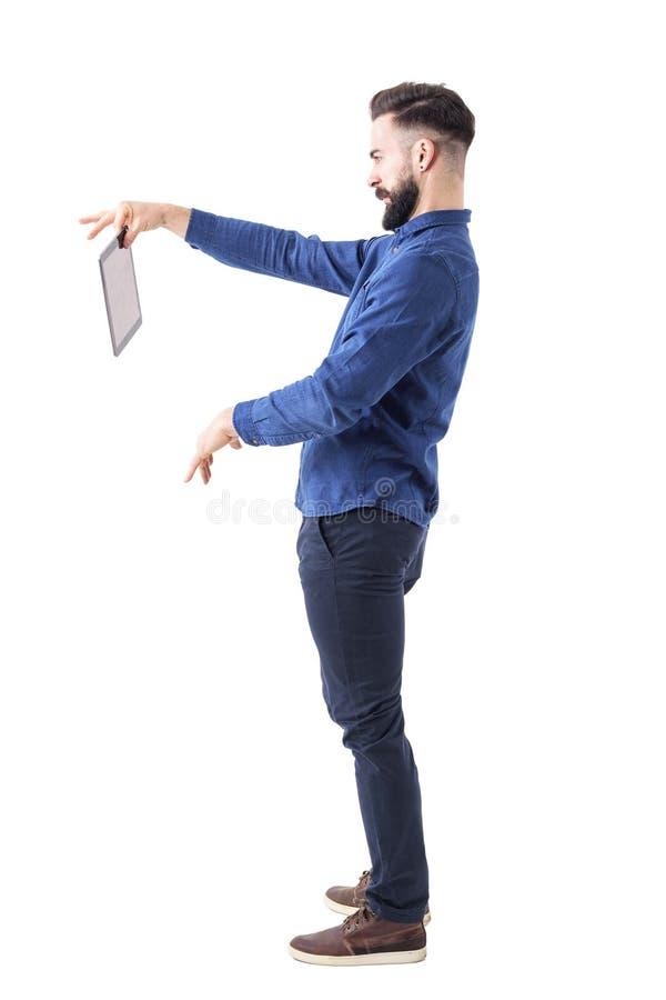 Homem de negócio farpado enojado que guarda a tabuleta com uns mão e dedo dois Vista lateral fotografia de stock