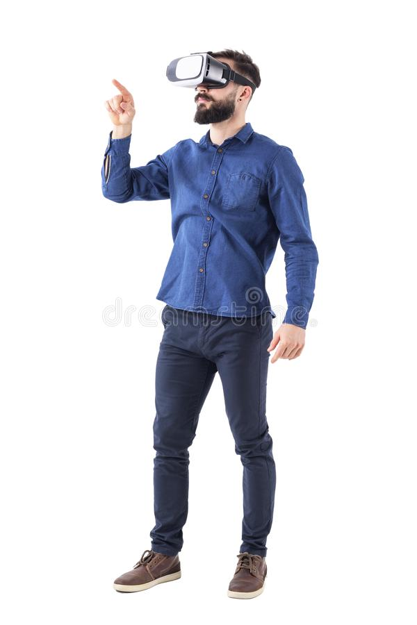 Homem de negócio farpado novo que veste a realidade virtual usando o dedo no tela táctil aumentado da realidade fotos de stock