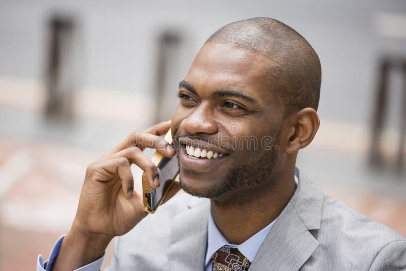 Homem de negócio feliz considerável que fala no telefone celular imagem de stock