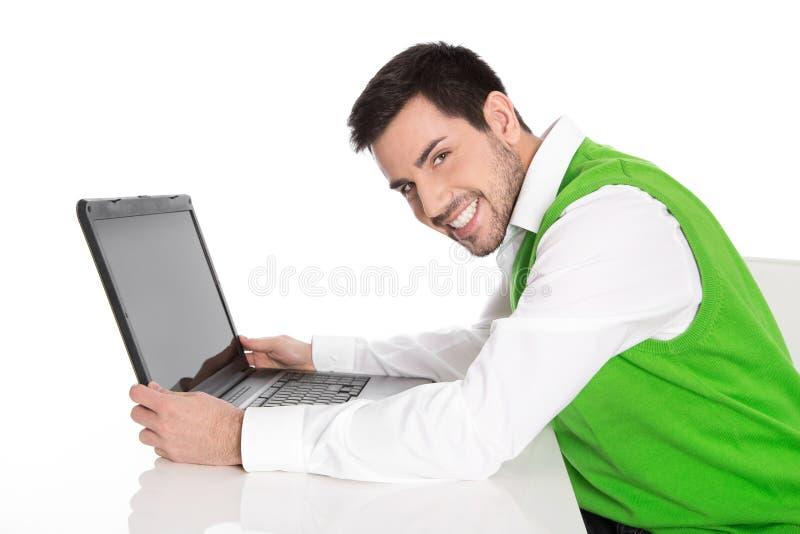 Homem de negócio feliz isolado no verde que guarda seu portátil fotografia de stock