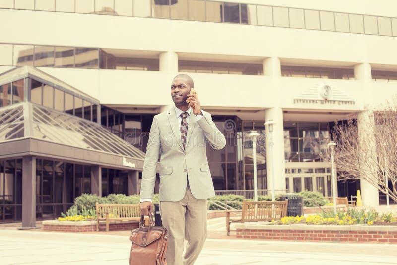 Homem de negócio feliz que fala em seu telefone ao andar fora foto de stock royalty free