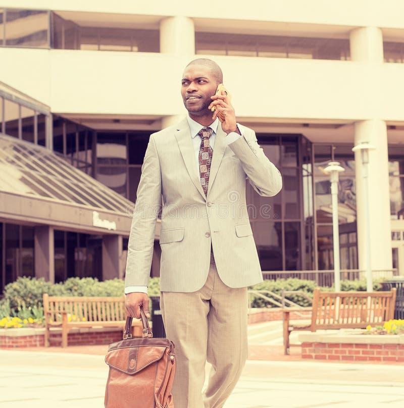 Homem de negócio feliz que fala em seu telefone ao andar fora fotografia de stock
