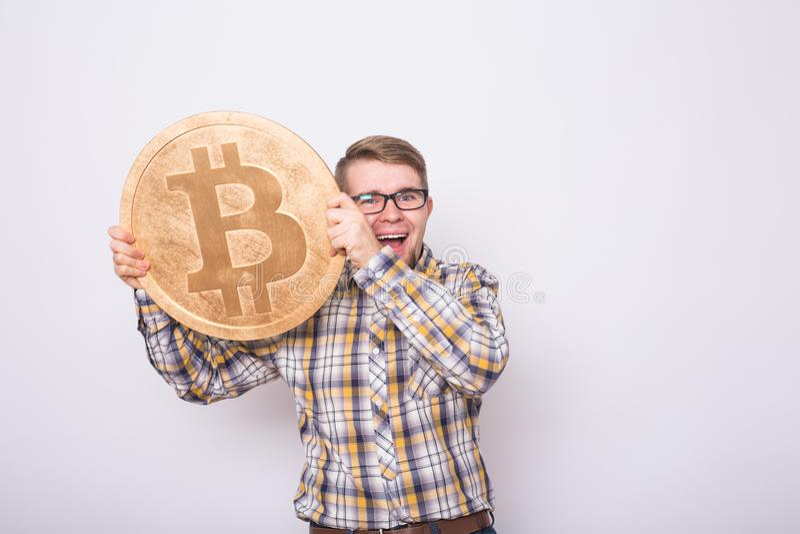 Homem de negócio feliz que guarda o bitcoin dourado grande no fundo branco Moeda cripto, dinheiro virtual, Internet e imagens de stock royalty free