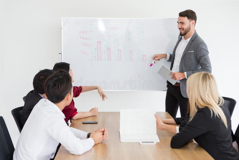 homem de negócio feliz que sorri e que faz uma apresentação no whiteboard e que aponta na carta chefe que apresenta a estratégia  imagem de stock