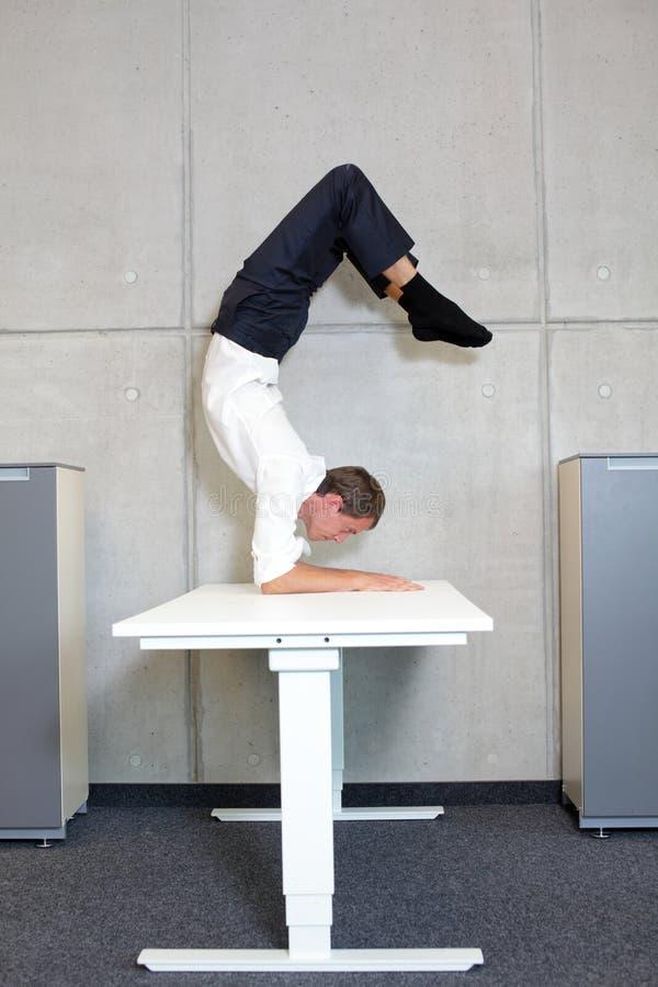 Homem de negócio flexível no asana do escorpião na mesa em seu escritório fotografia de stock