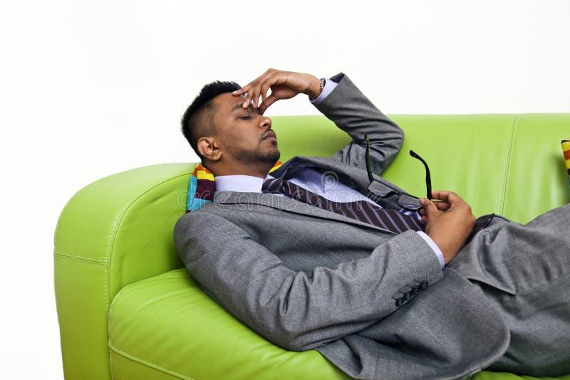 Homem de negócio forçado que guarda a ponte de seu nariz fotografia de stock