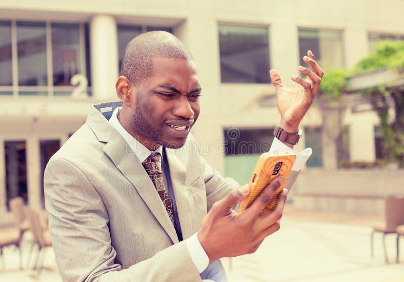 Homem de negócio frustrante que recebe más notícias no telefone celular fotografia de stock