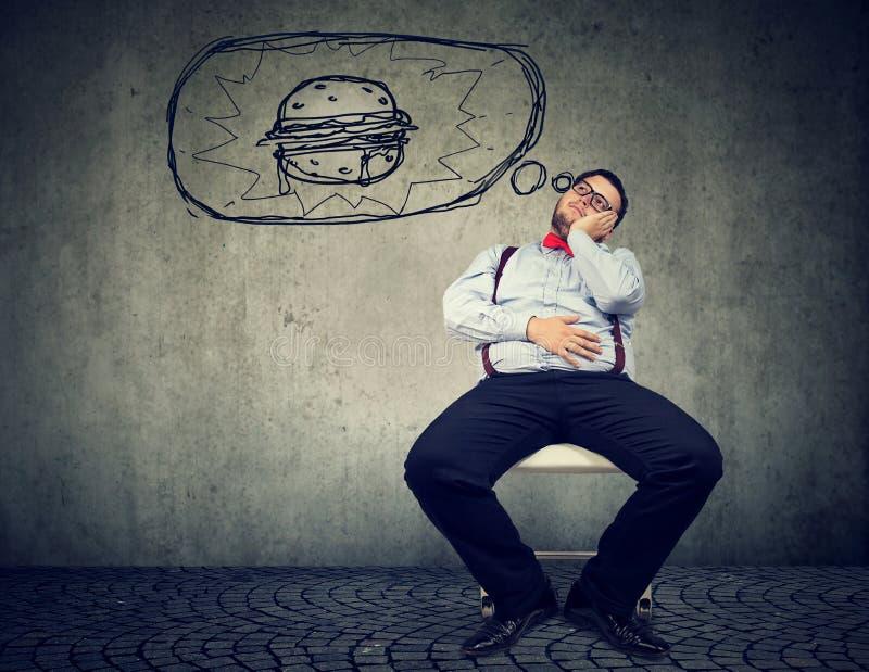 Homem de negócio gordo com fome que sonha de um hamburguer foto de stock royalty free