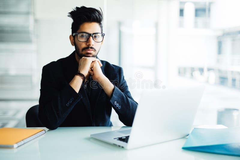 Homem de negócio indiano que usa o portátil com mão das mãos no queixo em seu escritório moderno fotografia de stock royalty free