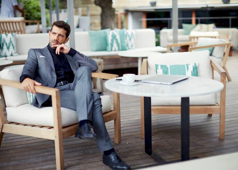 Homem de negócio inteligente bem sucedido que relaxa em um restaurante luxuoso fora fotografia de stock