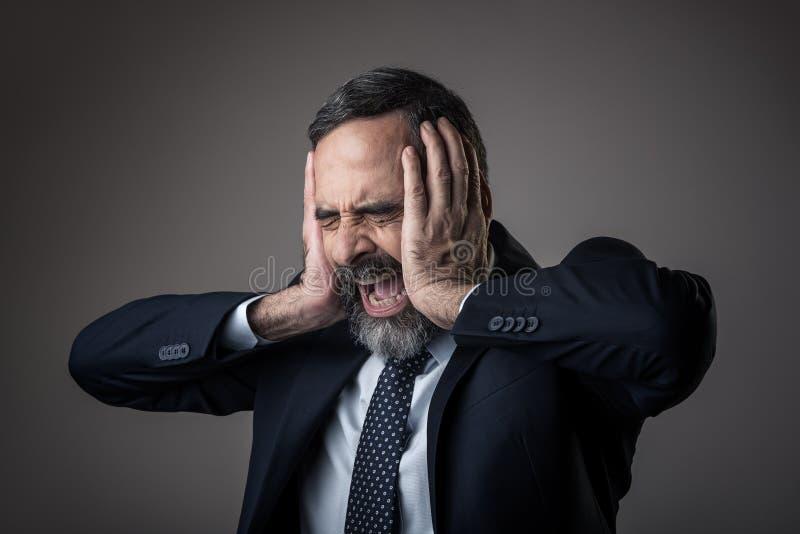 Homem de negócio irritado com uma dor de cabeça terrível fotos de stock royalty free