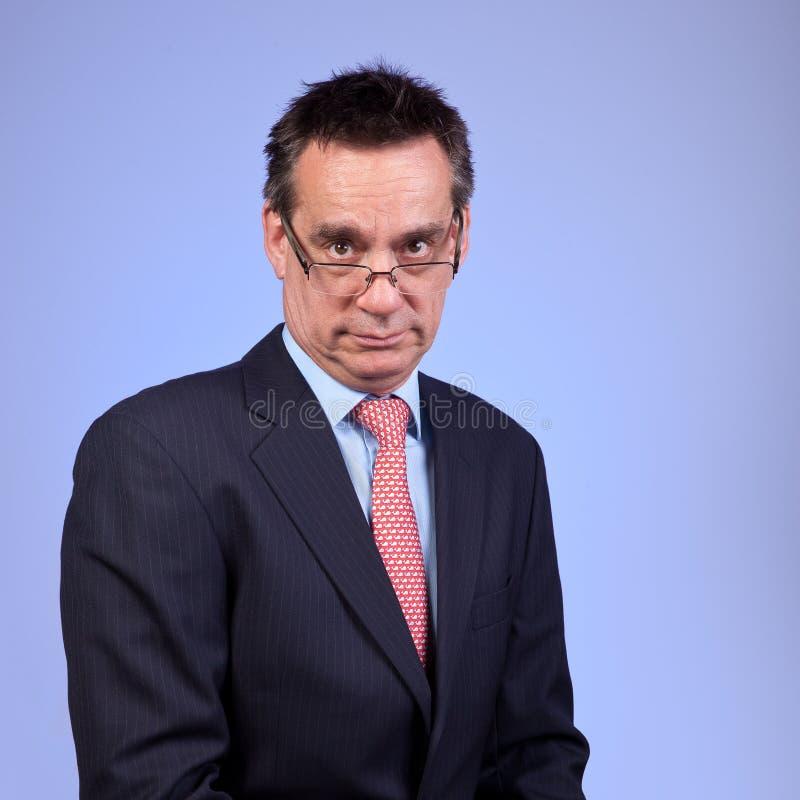Homem de negócio irritado olhando de sobrancelhas franzidas mal-humorado no azul fotos de stock royalty free