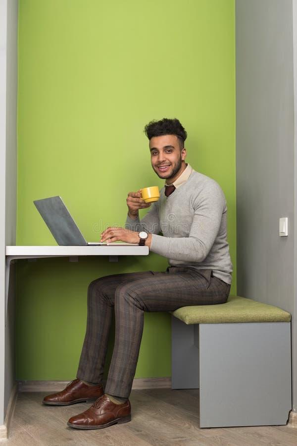Homem de negócio latino-americano que usa o copo da posse do café de In Coworking Center do homem de negócios do laptop imagem de stock royalty free