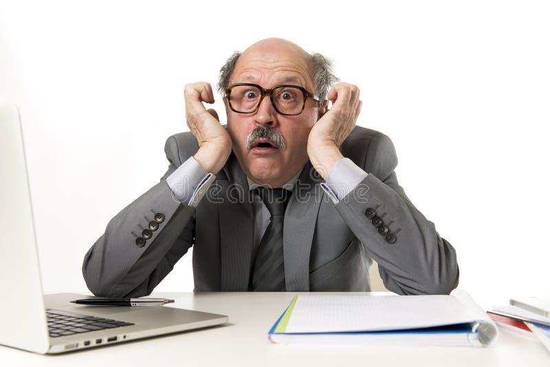 Homem de negócio maduro com cabeça calva em seu funcionamento 60s forçado e frustrado em parecer desesperado da mesa do portátil  fotos de stock royalty free