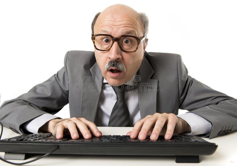 Homem de negócio maduro com cabeça calva em seu funcionamento 60s forçado e surpreendido na mesa do portátil do computador de esc foto de stock royalty free