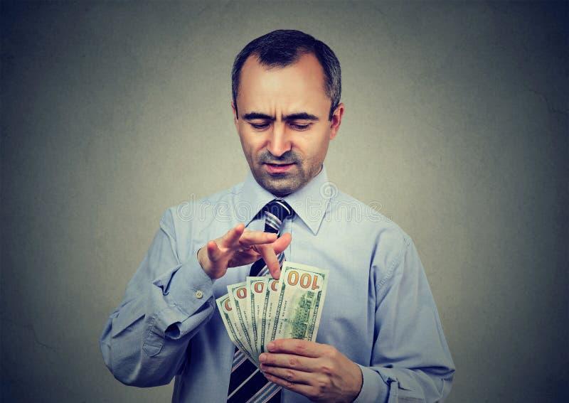 Homem de negócio maduro que conta o dinheiro imagens de stock