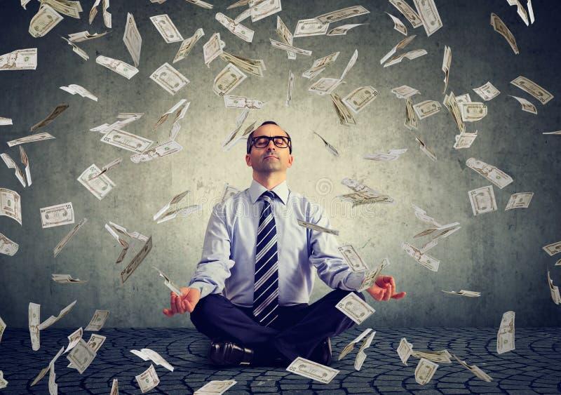Homem de negócio maduro que medita sob a chuva do dinheiro foto de stock