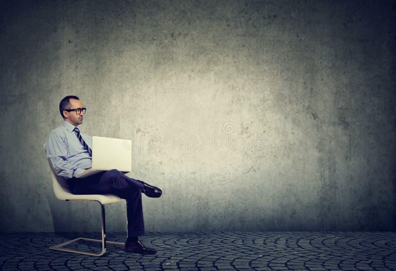 Homem de negócio maduro sério pensativo que usa o portátil que trabalha da casa fotografia de stock royalty free