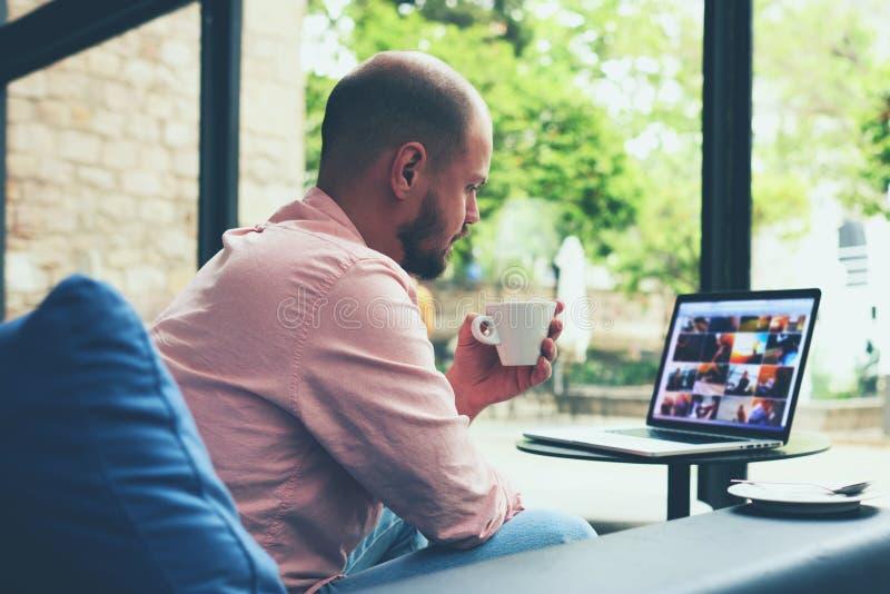 Homem de negócio moderno que conecta ao rádio em seu laptop durante a ruptura de café fotos de stock royalty free