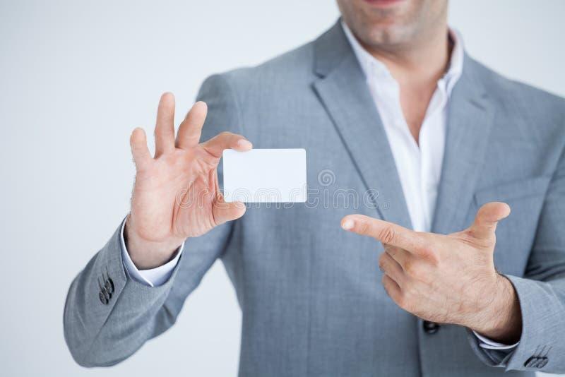 homem de negócio na mostra dos ternos ou em guardar e em apontar o dedo anular o modelo branco do cartão de crédito isolado no fu fotografia de stock royalty free