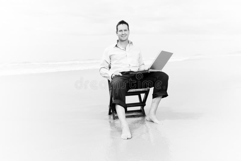 Homem de negócio na praia com portátil imagem de stock