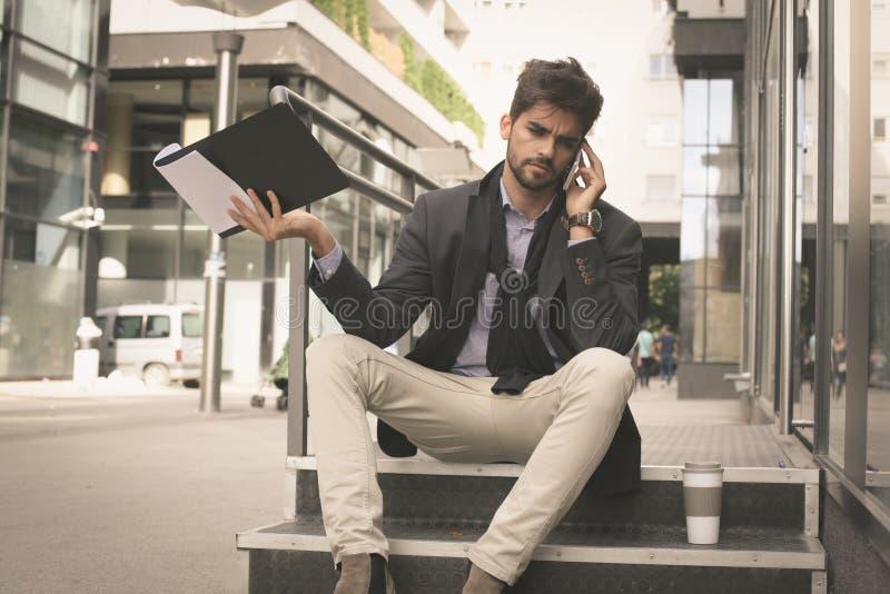 Homem de negócio na rua que tem a conversação séria no mo imagens de stock royalty free