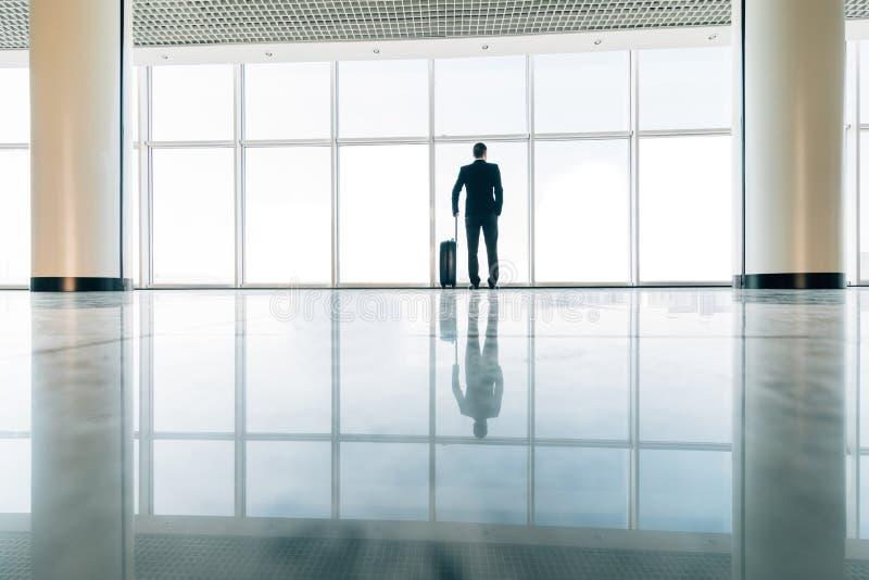 Homem de negócio no aeroporto com voo atrasado de espera da mala de viagem perto da porta Curso de negócio fotos de stock royalty free