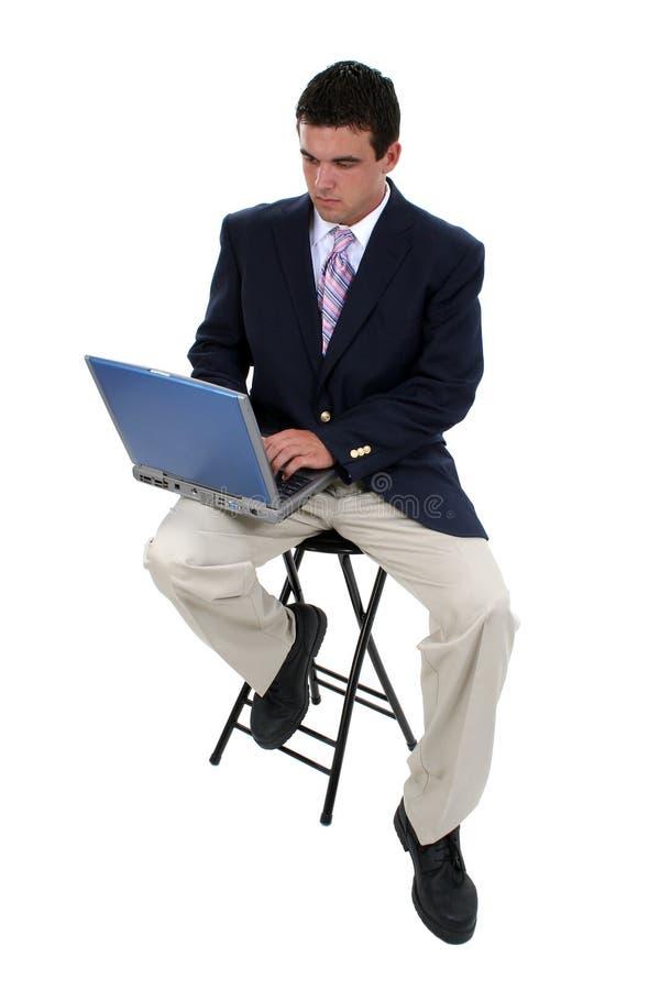 Homem de negócio no tamborete com portátil
