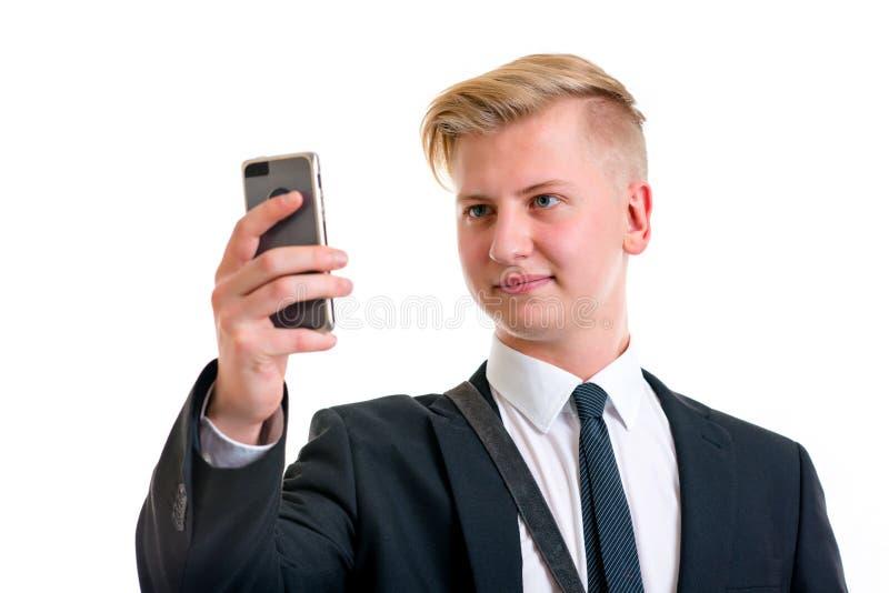 Homem de negócio no terno preto que toma um autorretrato com seu telefone imagens de stock