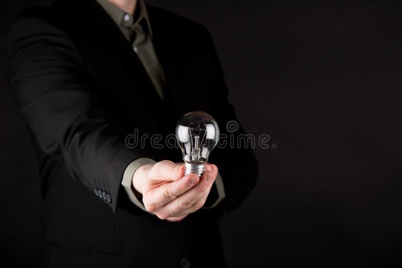 Homem de negócio no terno que guarda uma ampola tradicional à disposição, isolado no fundo do preto do inclinação foto de stock royalty free