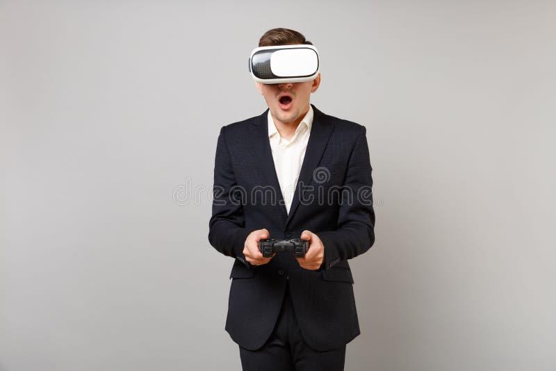 Homem de negócio novo chocado que olha nos auriculares, jogando o jogo de vídeo com o manche, mantendo aberto largo da boca isola fotos de stock