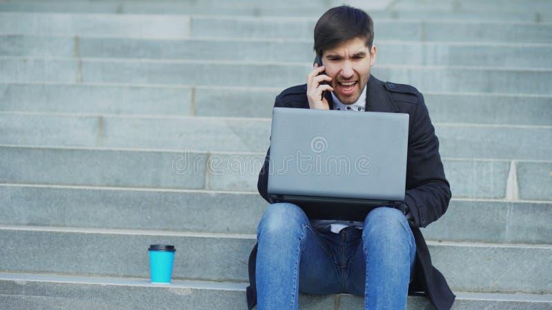 Homem de negócio novo com o laptop que tem o esforço após o telefonema e que senta-se em escadas na rua Homem de negócios fotografia de stock