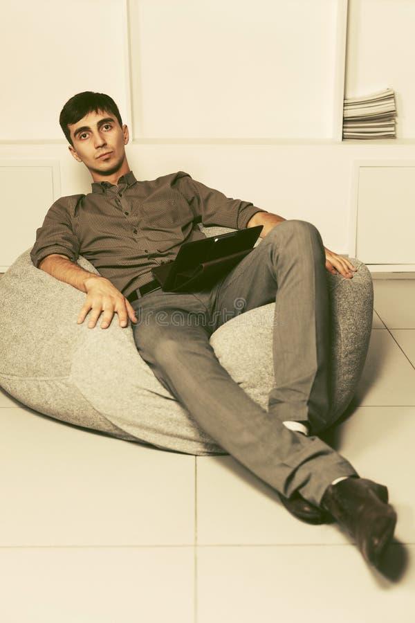 Homem de negócio novo com o tablet pc digital que senta-se na cadeira imagem de stock