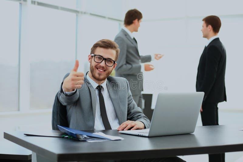 Homem de negócio novo considerável com os povos no fundo na reunião do escritório Mostrando os polegares acima fotos de stock