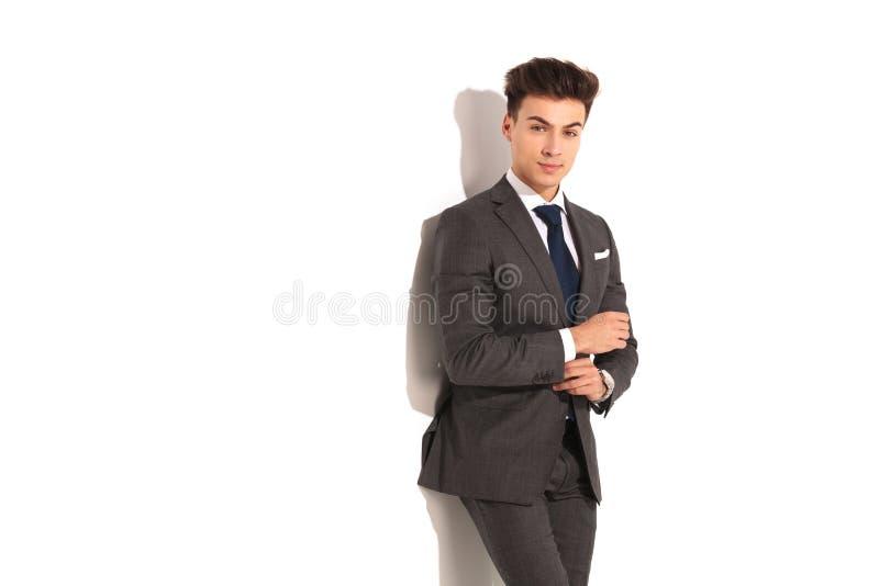 Homem de negócio novo considerável que fixa sua luva foto de stock