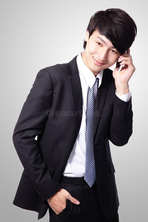 Homem de negócio novo considerável que usa o telemóvel imagem de stock